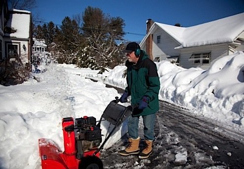 Middle-aged man pushing snowblower