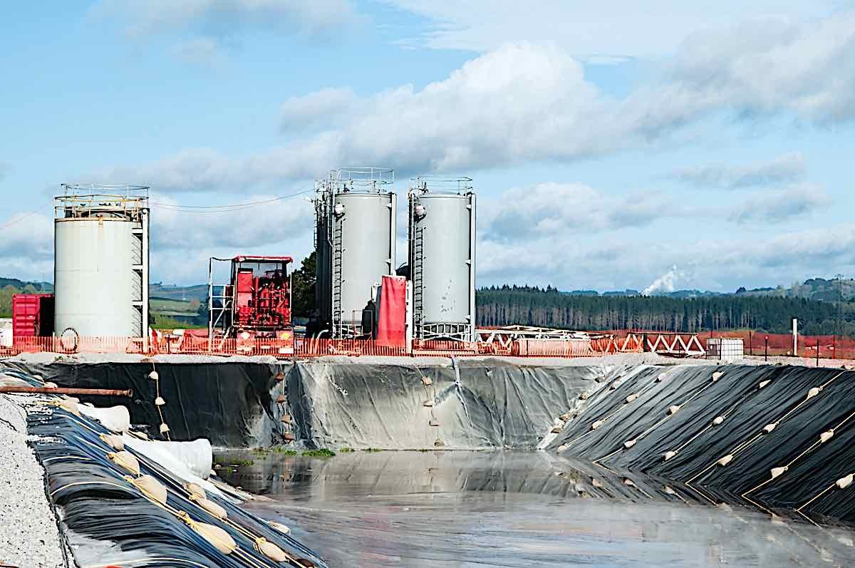 Engineered Design Insider Geosynthetically lined Drilling liquid storage reservoir with storage silos and geothermal steam on horizonOil Gas Automotive Aerospace Industry Magazine